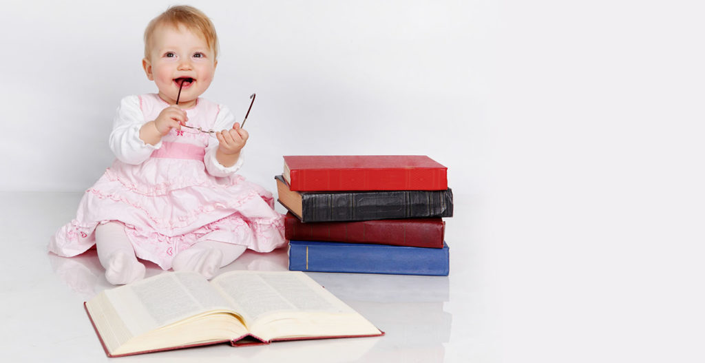 Baby sitting with books at a Preschool & Daycare Serving Houston & Cypress, TX